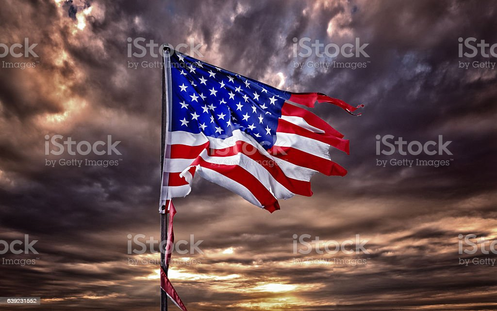 Tattered American flag flapping in ominous sky stock photo