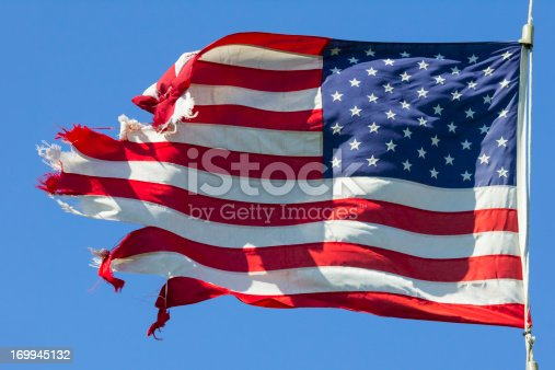 Tattered American Flag, Still Flying Free and Proud.  This image is symbolic of the American spirit, even when tired and rough around the edges, America goes forward.