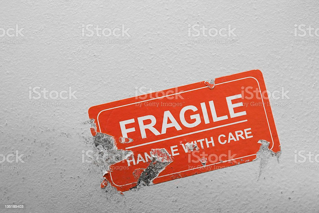 Tattered red fragile handle with care sticker on a wall stock photo