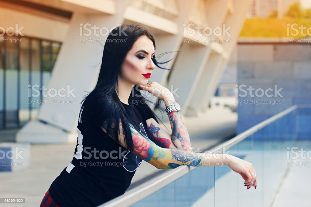 Tattoed beauty. Portrait of attractive tattoed hipster girl standing against urban background. royalty-free stock photo