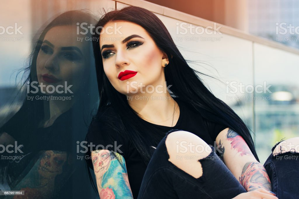 Tattoed beauty. Portrait of beautiful attractive tattoed hipster girl posing to camera while sitting against urban background. royalty-free stock photo