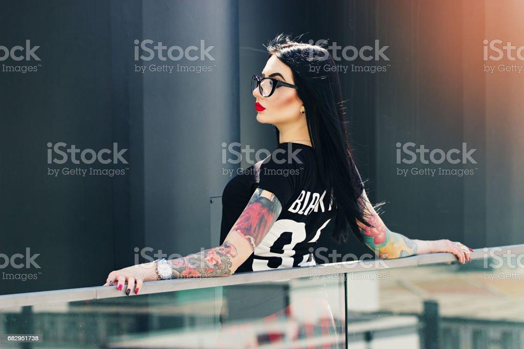 Moda de tatuado. Retrato de muchacha de inconformista tatuado atractiva posando a la cámara sobre fondo urbano. foto de stock libre de derechos