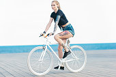 A tattooed woman who embraces the beauty and grace of her body is riding a bicycle (a fixed gear bicycle) at the seaside in Barcelona, Catalonia. She is not afraid to show her body art, riding the bike in short blue jeans and a tied up little black tee she allows others to see the gorgeous tattoos covering her arms, torso and legs. She rides her white fix right next to blue sea.