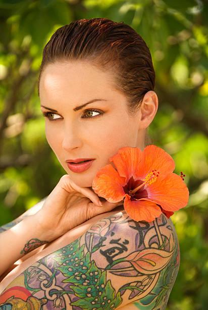 tattoed frau mit blume. - hibiskus blume tattoos stock-fotos und bilder
