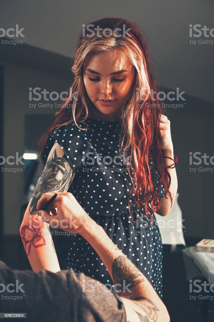 Tattoo artist creating a tattoo on a girl's arm stock photo