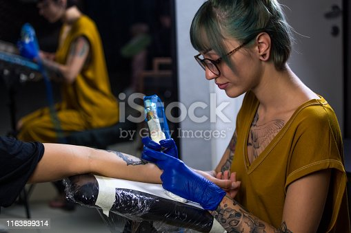 istock Tattoo artist demonstrates the process of getting black tattoo with paint. Master works in blue sterile gloves. Master of tattoo fill circuit tattoo. 1163899314