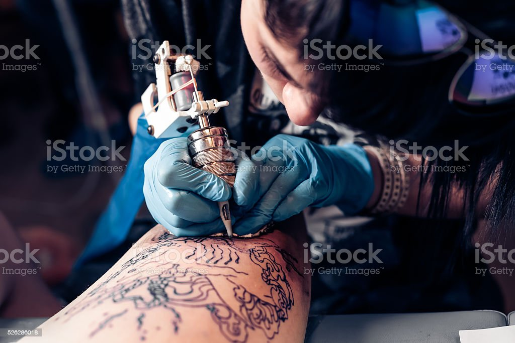 Tattoo artist demonstrates the process of tattoo stock photo