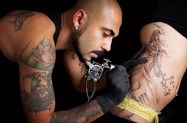 A tattoo artist giving a customer a tattoo stock photo