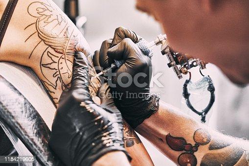 istock Tattoo Artist making a tattoo on a shoulder 1184219605