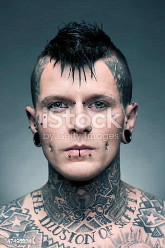Portrait of a young man with a lot of tattoos and piercings