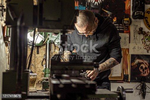 istock Tattoo artist preparing his machine in the studio 1217415675