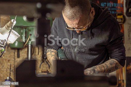 istock Tattoo artist preparing his machine in the studio 1217416283