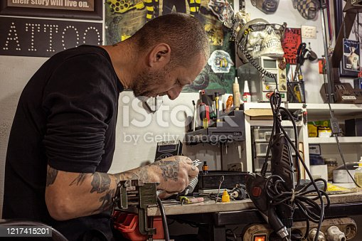 istock Tattoo artist repairing tattoo machine in his workshop 1217415201