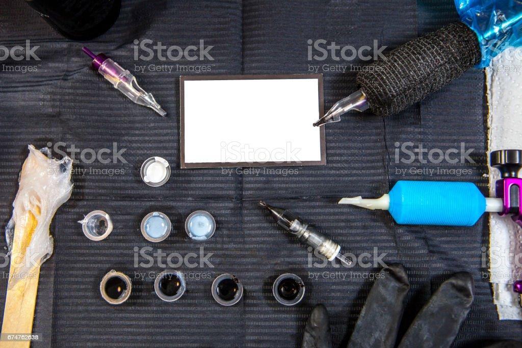 Tattoo-Künstler-Tabelle mit Objekten und Leere Visitenkarte in der Mitte – Foto