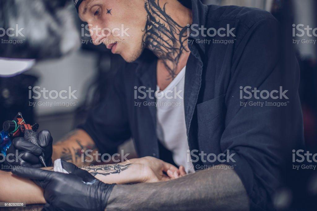 Tattoo artist tattooing stock photo