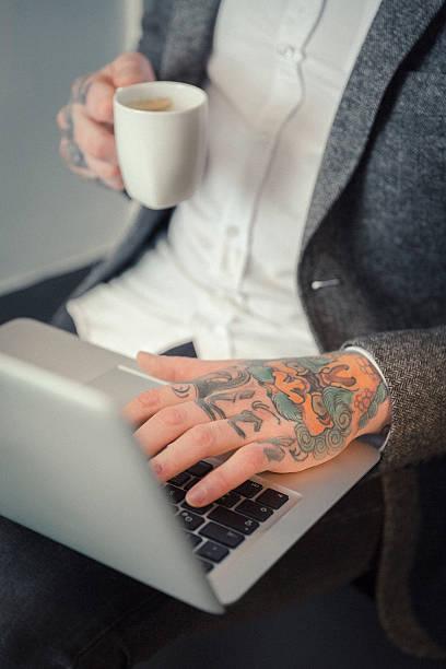 tattoo artist mit laptop-computer in studio - kaffeetasse tattoo stock-fotos und bilder