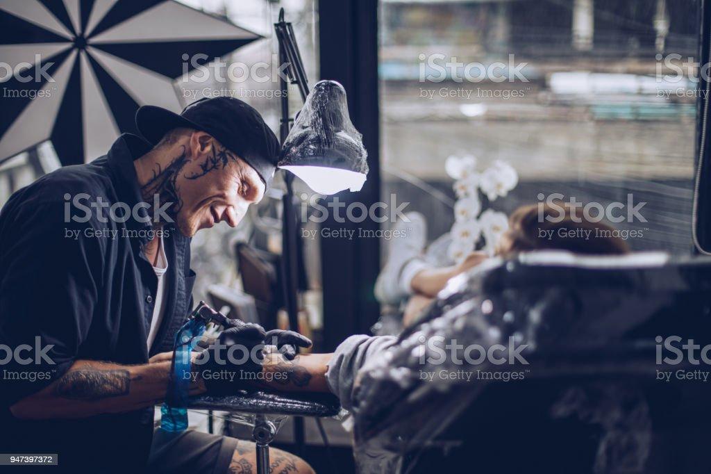 Tattoo artist working hard stock photo