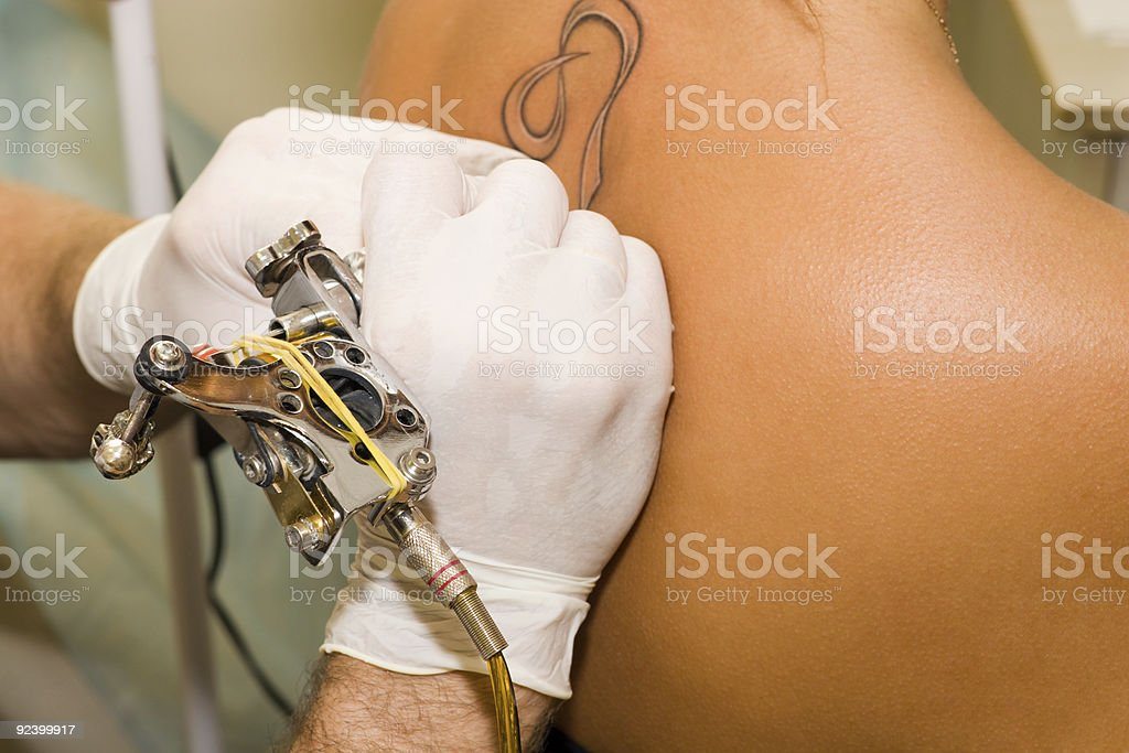 Tattoo artist working on a tattoo on someone's back  royalty-free stock photo