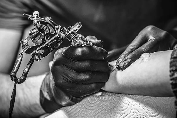 Tattoo artist working stock photo