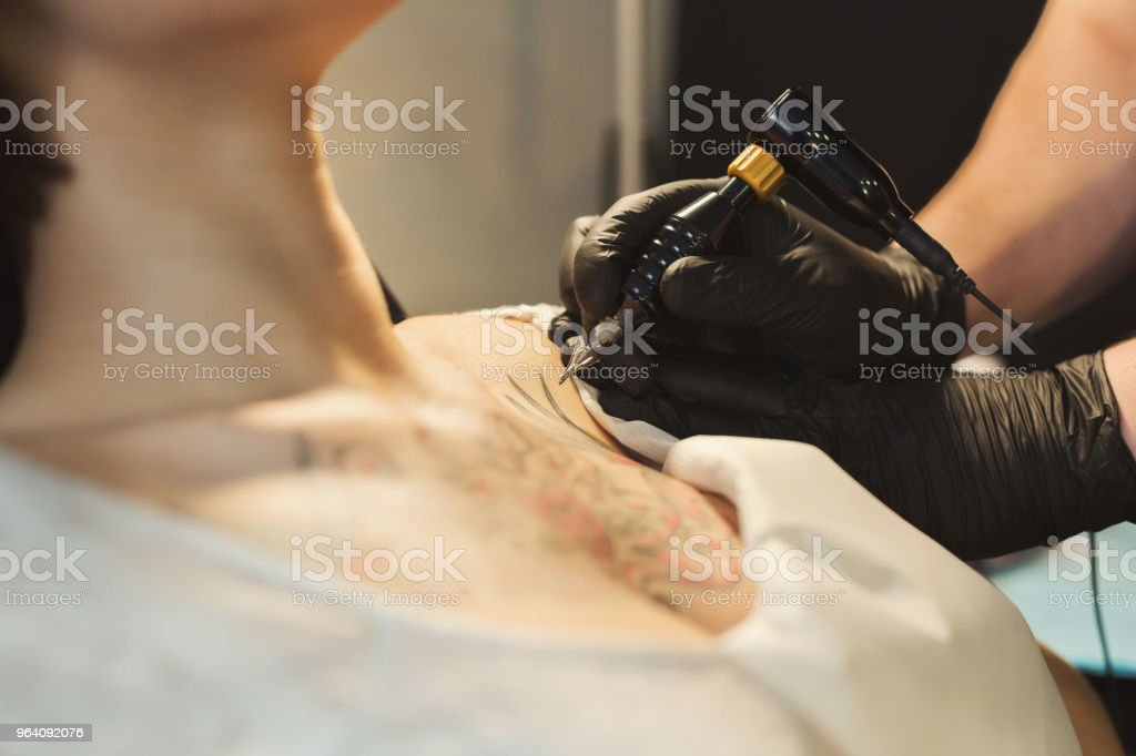 Tattoo artist working with needle on clients body - Royalty-free Adult Stock Photo