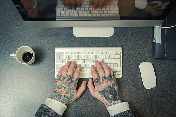 tattoo artist's hände mit computertastatur - kaffeetasse tattoo stock-fotos und bilder
