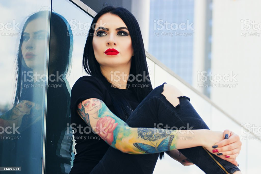 Tattoo fashion. Portrait of fashionable tattoed hipster girl with red lips sitting against urban background. royalty-free stock photo