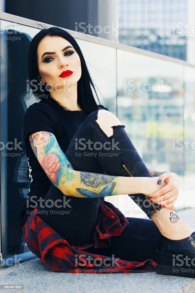 Tattoo fashion. Portrait of fashionable tattoed hipster girl with red lips posing against urban background. royalty-free stock photo