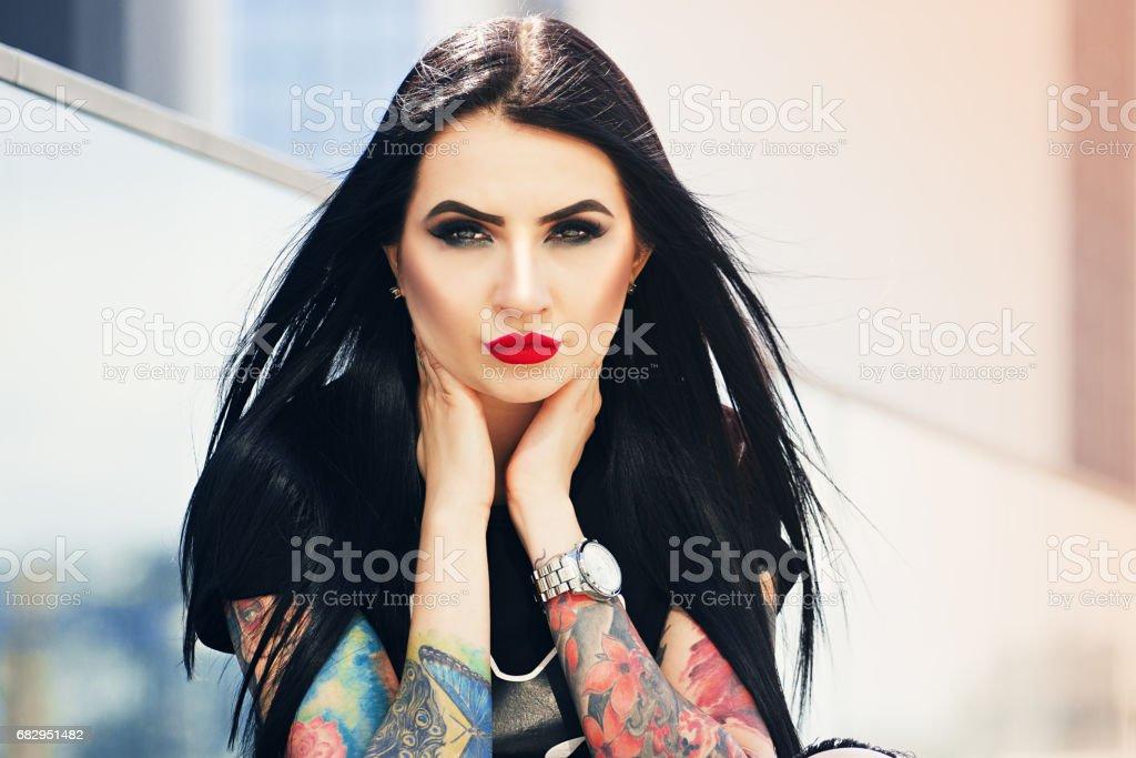 Moda del tatuaje. Retrato de niña de hipster estilo tatuado en tocar su cara mientras que se coloca en contexto urbano. foto de stock libre de derechos