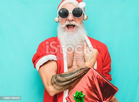 istock Tattoo fit Santa Clause with gift box wearing funny fest sunglasses  - Fashion senior man with winter holiday costume - Winter, trends, party concept - Soft focus on his mouth 1066159402