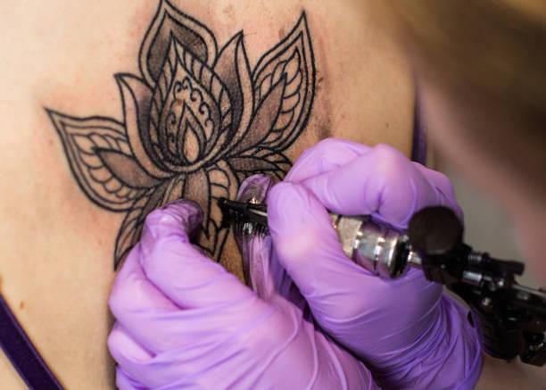 tattoo blume am rücken der frau - lotus zeichnung stock-fotos und bilder
