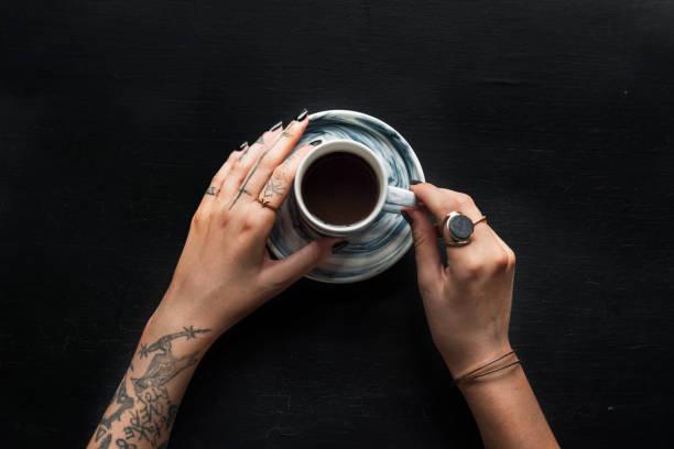 tattoo hand mit kaffeetasse getränk - kaffeetasse tattoo stock-fotos und bilder