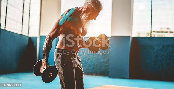 Tattoo male athlete doing workout session inside wellness club center - Fitness man working with dumbbell in functional training gym - Body building and sport trends concept - Focus on his face