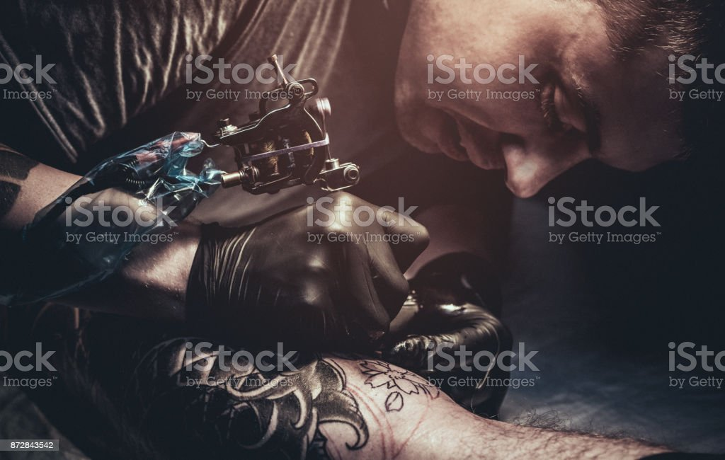 Tattoo master making tattoo on customer's leg stock photo