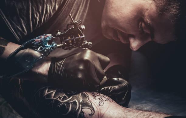 tattoo-meister machen tattoo am bein des kunden - männliche körperkunst stock-fotos und bilder