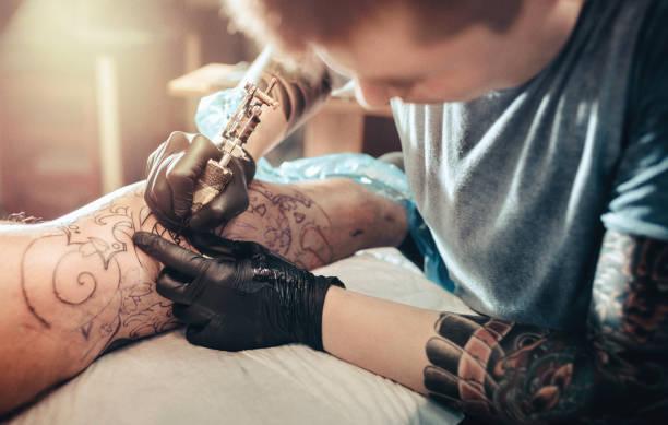 Tattoo-Meister machen Tattoo am Bein – Foto