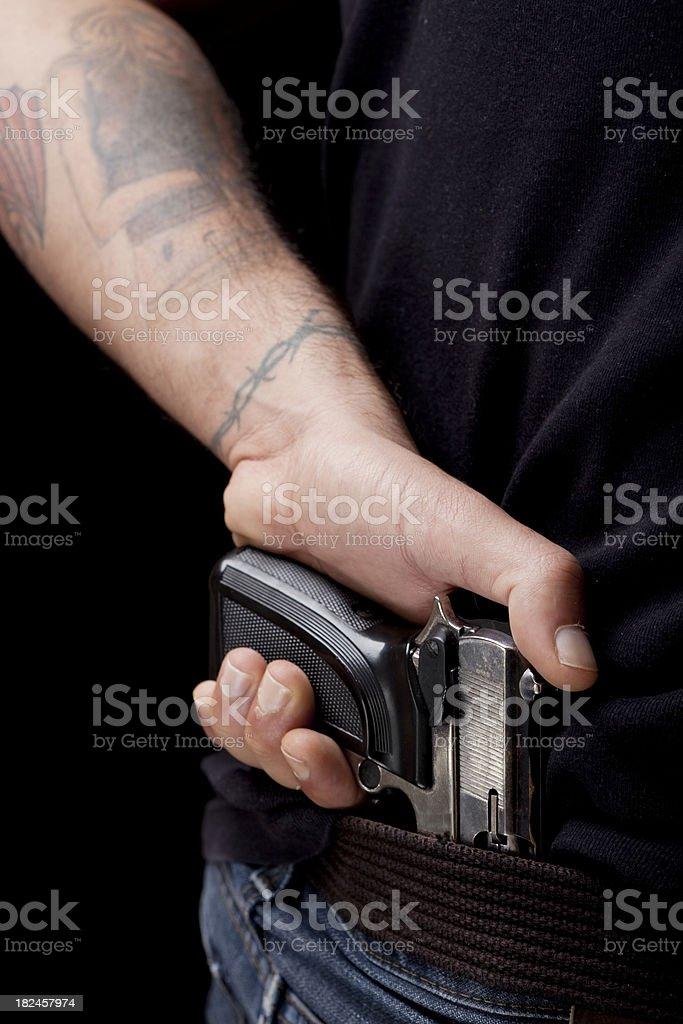 Tattooed sosteniendo una pistola brazo de borde interior de blue jeans. foto de stock libre de derechos