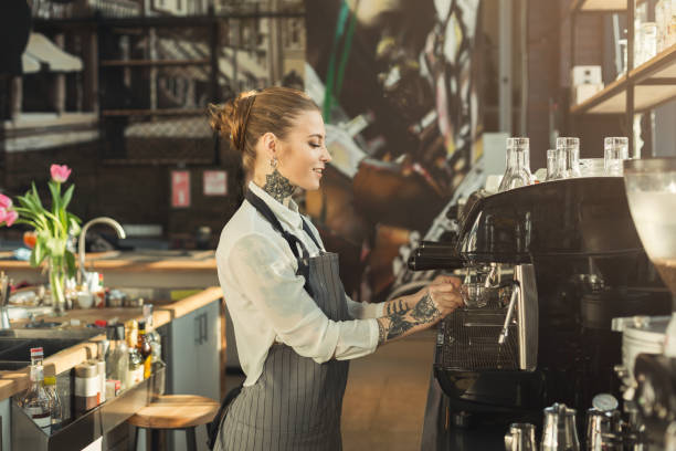 tattooed barista making coffee in professional coffee machine - barista making coffee stock photos and pictures