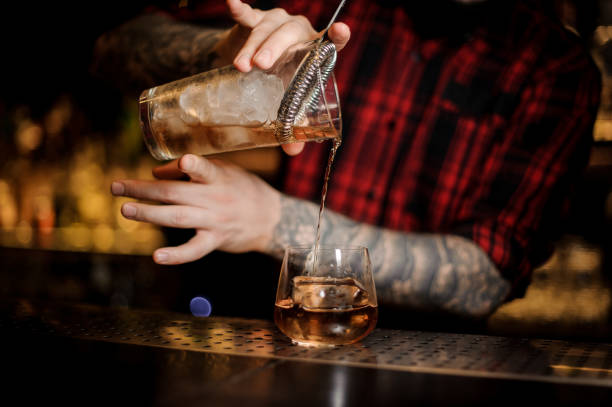 Tattooed barman pouring fresh drink into a whiskey dof glass Tattooed barman pouring fresh and cold drink into a whiskey dof glass on the bar counter bartender stock pictures, royalty-free photos & images