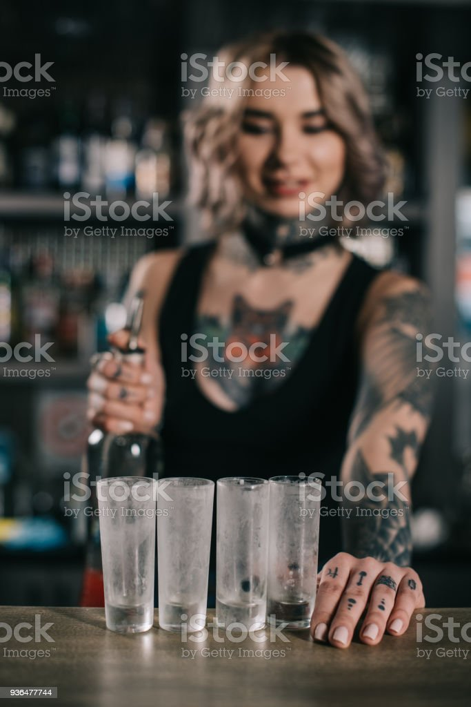 Tattooed Bartender Looking At Glasses For Shot Drinks Stock Photo