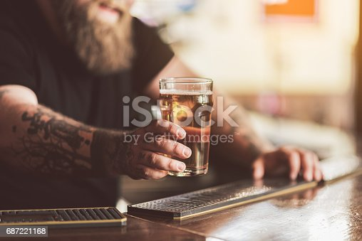 istock Tattooed bartender with beard working in pub 687221168
