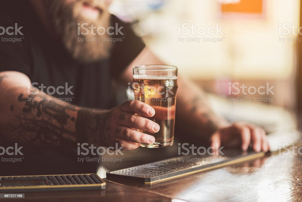 Tattooed bartender with beard working in pub stock photo
