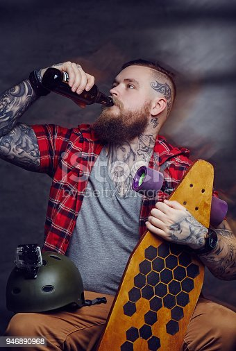 istock Tattooed bearded hipster skateboarder drinking beer. 946890968