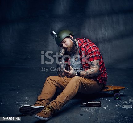 983236144istockphoto Tattooed bearded hipster skateboarder drinking beer. 946894148