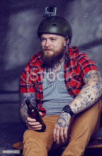 istock Tattooed bearded hipster skateboarder drinking beer. 946894332