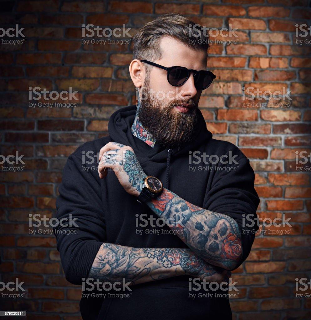 Macho barbudo tatuado no casaco militar. - foto de acervo