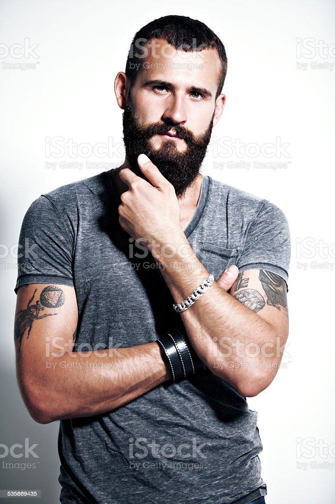 Tattooed bearded man wearing gray t-shirt stock photo