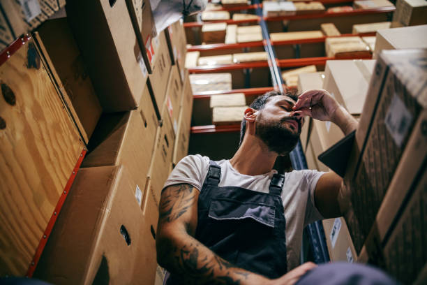 Tattooed bearded worker in overalls having hard day on the work. Storage of import and export firm interior. stock photo