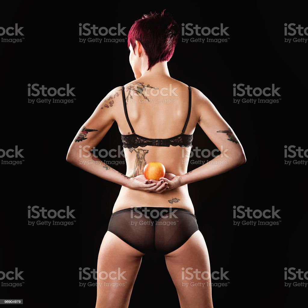 Tattooed Beautiful Woman Holding Apple Behind Her Back royalty-free stock photo
