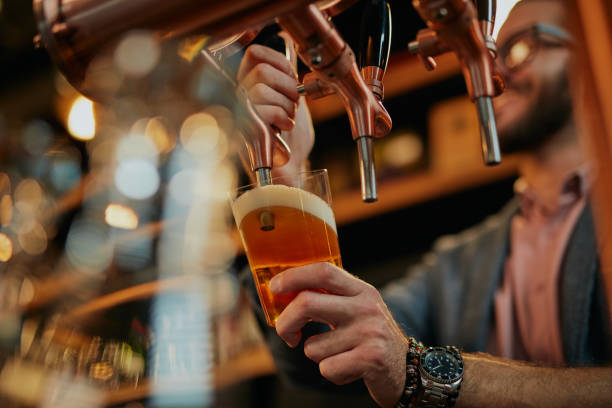 Tattooed caucasian barman pouring beer while standing in pub. stock photo