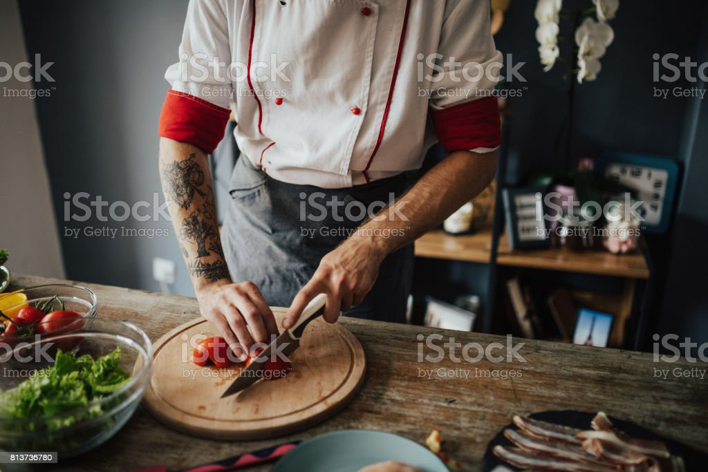 Tattooed chef cuts tomato into round slices stock photo